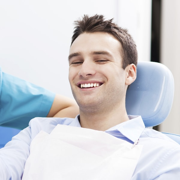 Young man sitting in a blue dental treatment chair about to get restorative dentistry