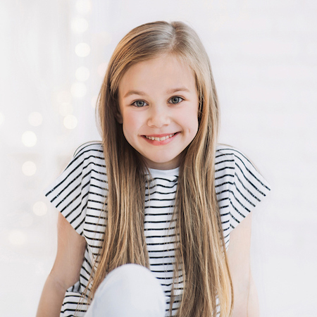 A young girl with long hair and striped top receiving family dentistry