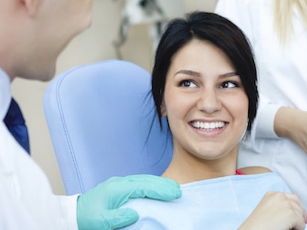 Woman with dark hair sitting in dental chair as she is about to choose from our services