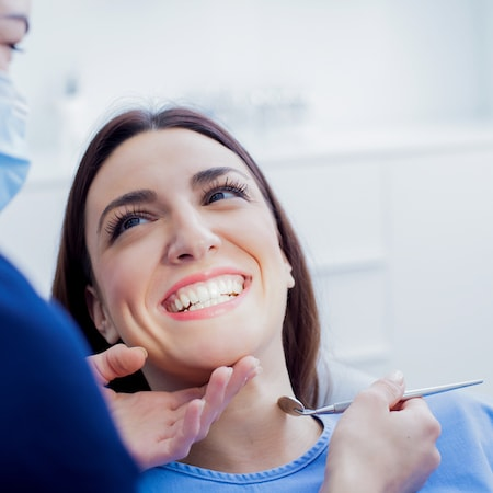 A close up of a woman in a dental chair smiling while getting family dentistry