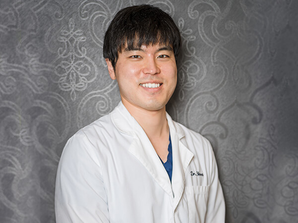 One of our dentists, Dr. Yoon smiling in his white dental coat